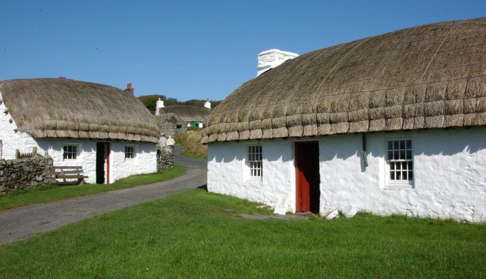 An image of the thatched cottages in Cregneash village on a summer's day. The sky is blue and the sun is shining.