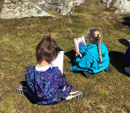Two school children drawing pictures in the countryside, at Meayll Circle