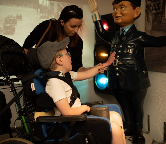 A visitor in a wheel chair is touching the model of a policeman in the Manx Museum's play gallery The Exploratorium.