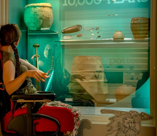 A young female visitor in a wheel chair looking at a archaeological collections in the Manx Museum Prehistory Galley.